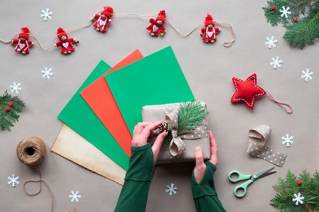 Ноль отходов рождества, плоская планировка, вид сверху на крафт-бумагу - текстильная кукольная гирлянда, завернутые подарки, руки украшают подарочную коробку ручной работы на страницах цветной бумаги. экологически чистая альтернатива зелёному рождеству.