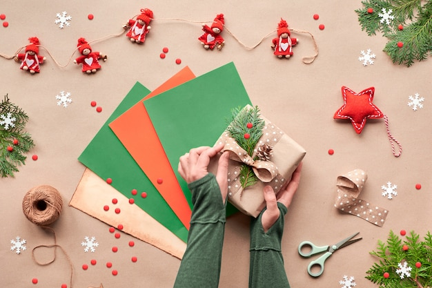ゼロ無駄なクリスマス、フラット横たわっていた、クラフトペーパーバックグラウンドのトップビュー。テキスタイルドールガーランド、テキスタイルスター、手はカラーペーパーのページに手作りのギフトボックスを飾ります。エコフレンドリーな代替グリーンクリスマス。