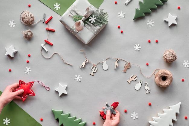 廃棄物ゼロのクリスマス、フラット横たわっていた、クラフト紙の背景のトップビュー-テキスタイルドールガーランド、ラップされたギフトボックス、女性の手は赤いテキスタイルスターと人形を保持します。