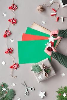 環境に優しい代替クリスマス。廃棄物ゼロのクリスマス、フラットレイ、クラフトペーパーテキスタイルドールガーランドのトップビュー、星、テキストまたはレタリングのためのコピースペースで色紙を保持します。