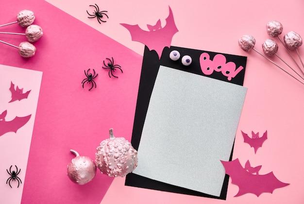 Креативная бумажная поделка на хэллоуин плоско лежала в розовом, светло-фиолетовом и черном цветах. вид сверху с копией пространства на стопку карт, летучие мыши, шоколадные глаза и декоративные тыквы.