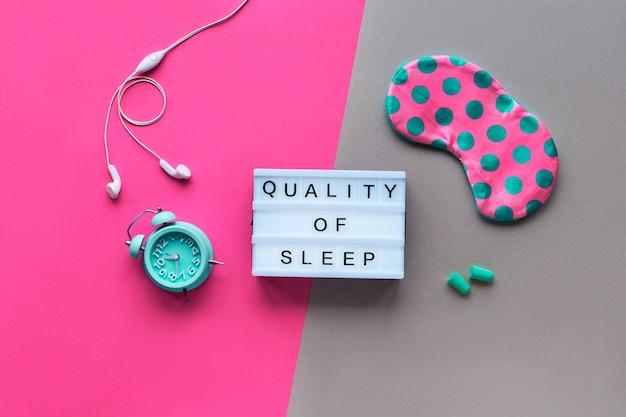 ライトボックスのテキスト「睡眠の質」。タイルグリーンの水玉、目覚まし時計、イヤホン、耳栓のピンクの睡眠マスク。フラットレイ、トップビュー、スプリットツートーンピンクとクラフト