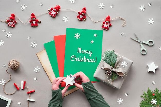 テキスタイル人形のガーランド、グリーティングテキスト「メリークリスマス」とカラーペーパーを保持している女性の手。環境に優しい代替クリスマス。クリスマスを無駄にしません。