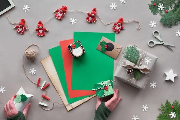 環境に優しい代替クリスマス。ゼロ無駄なクリスマス、フラット横たわっていた、クラフトペーパーバックグラウンドのトップビュー。織物人形のガーランド、星、手は紙の装飾を保持します。いくつかの創造的な装飾ボックス。