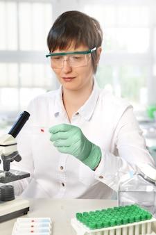 中年の女性科学者が研究室で働いています