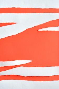 サンゴ色の紙の背景にコピースペースで白い紙の引き裂かれたストライプ