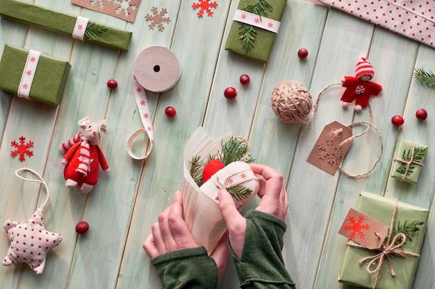 さまざまなクリスマスまたは新年の冬休みの環境に優しい装飾、クラフト紙パッケージ、再利用可能な、または廃棄物ゼロのギフト。フラットは、木の上に横たわり、緑の葉で手作りの装飾を作る手。