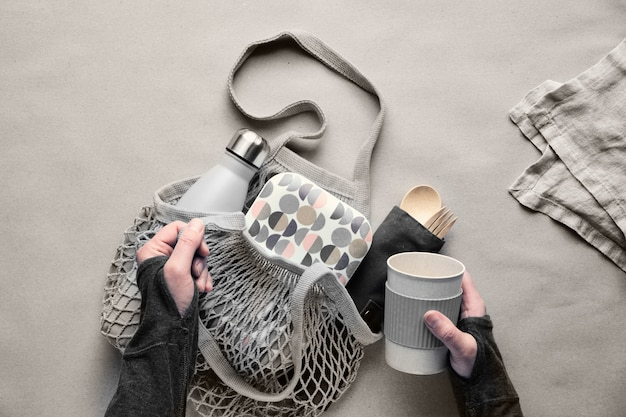 廃棄物ゼロのランチキット、コットンバッグにセットしたテイクアウトランチボックス、竹カトラリーのオーガナイザー、竹ランチボックス、再利用可能なカップ。持続可能なライフスタイル、幾何学的なフラットレイアウト、ペーパークラフトの平面図。