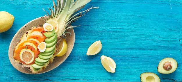 スモークサーモン、アボカド、レモン、ウズラの卵、パノラマ、コピースペースとパイナップルボートのトップビュー