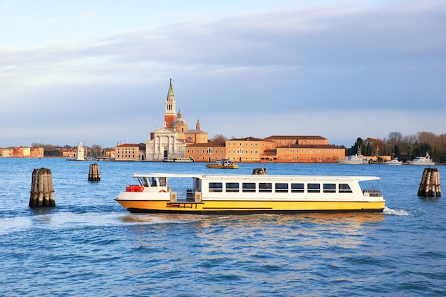 Желтый и белый туристический катер в лагуне венеция, италия
