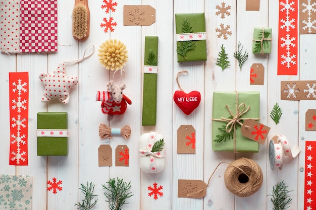 さまざまなクリスマスや新年の冬休み環境に優しい装飾、クラフトペーパーパッケージ、再利用可能なギフトのアイデア。リボン、コード、常緑樹で飾られたギフトボックスで幾何学的なフラットレイアウト