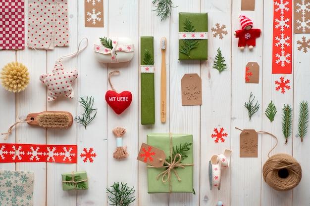 さまざまなクリスマスまたは新年の冬休みの環境に優しい装飾、クラフト紙のパッケージ、環境に優しいギフトのアイデア。リボン、コード、常緑樹で飾られたギフトボックスで幾何学的なフラットレイアウト