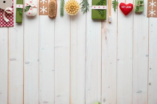 コピースペース、クラフトペーパーボックス、エコフレンドリーなギフトとクリスマスや新年の冬の休日のエコフレンドリーな装飾。リボン、コード、常緑樹で飾られたギフトボックスで幾何学的なフラットレイアウト