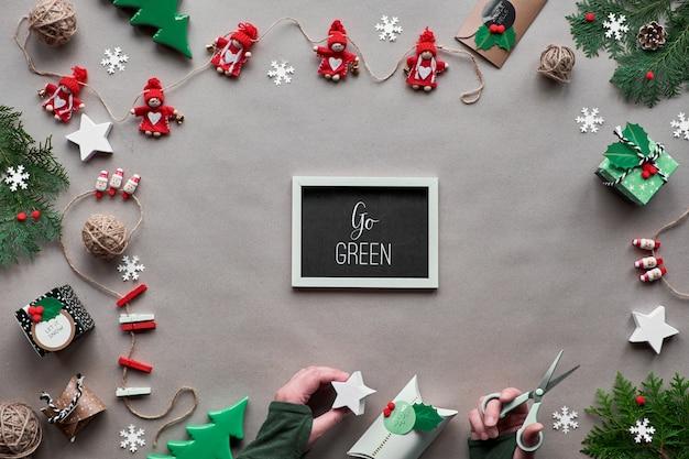 創造的な手作りの装飾、ゼロ廃棄物クリスマスフレーム。フラット横たわっていた、クラフトペーパーのトップビュー。繊維装身具、装飾紙ギフトボックスを手に。環境に優しいクリスマス。黒板にテキスト「緑に行く」。