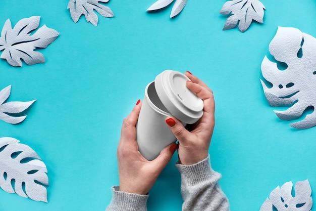 スタイリッシュな再利用可能なエココーヒー旅行マグカップ、手にふた付きの竹カップ。ホワイトペーパーエキゾチックな葉と青いミント紙の背景、ペーパークラフトゼロ廃棄物エコフレンドリーなライフスタイルの傾向。