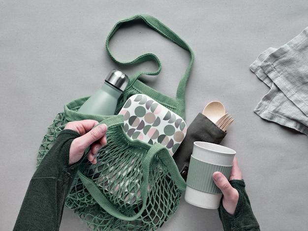 Упакованный ланч с нулевыми отходами, набор для ланча на вынос на хлопчатобумажной сумке, органайзер из бамбуковых столовых приборов, бамбуковая коробка для ланча и многоразовая чашка. устойчивый образ жизни, геометрическая планировка, вид сверху на крафт-бумагу.