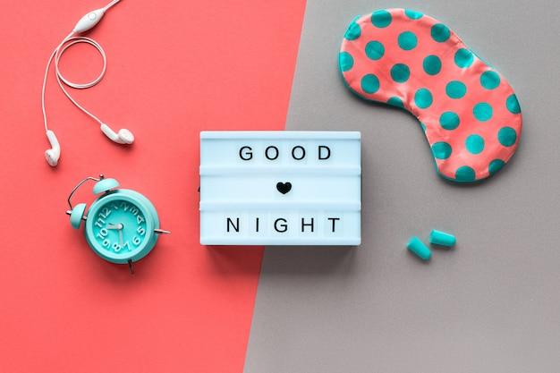 Текст «спокойной ночи» здоровый ночной сон креативная концепция. спальная маска в горошек, будильник, наушники и беруши. плоская планировка, вид сверху, двухцветная коралловая стена и бирюзовая бумага.