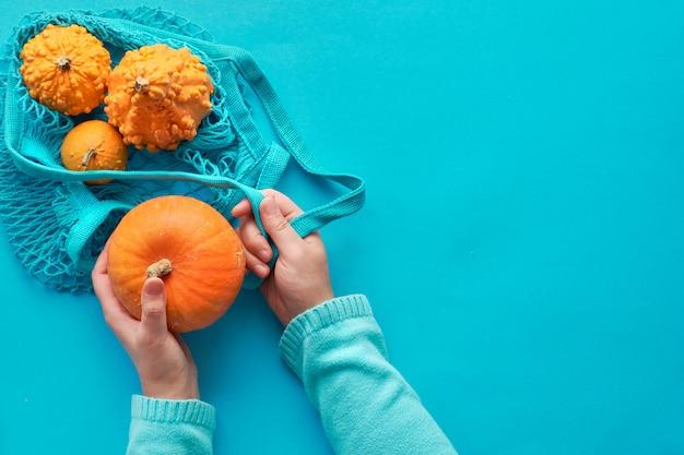ターコイズストリングバッグにオレンジ色のカボチャを入れて女性の手で横たわっている秋のフラット