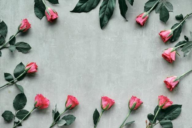 テキストの挨拶のためのスペースとバレンタイン、誕生日または母の日の概念。香りのよいピンクのバラで作られた自然の花のフレーム、フラットレイアウト、コピースペース付きの軽い石の壁のトップビュー。