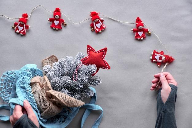 代替グリーンクリスマス、新年のコンセプトです。クラフトペーパーのフラット横たわっていた、トップビュー。本物の木を殺さずに偽の木で祝いましょう!メッシュバッグのプラスチック製のクリスマスツリー、環境に優しいクリスマスの装飾。