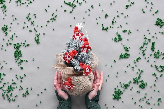 偽の偽のクリスマスツリーをできるだけ長く使用し続けます。代替グリーンエコフレンドリーなクリスマスコンセプト。手は、茶色のクラフト紙に黄麻布のメッシュでプラスチック粒子を包んだプラスチックの木を示しています。