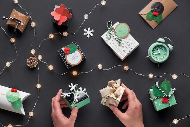 新年やクリスマスプレゼントは、お祝いタグが付いたさまざまな紙のギフトボックスに包まれています。ボックスを保持している手。お祝いのフラットレイアウト、黒い紙に軽い花輪、アラーム、紙雪片で平面図。