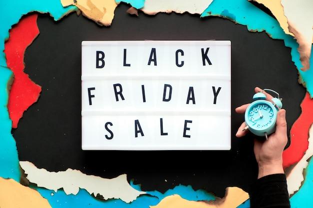 ライトボックステキスト「ブラックフライデーセール」に、縁が焼けた白、赤、黄色、青緑色の紙の焦げた紙の穴、黒い紙の創造的な壁、目覚まし時計を持っている黒いシャツを手に。