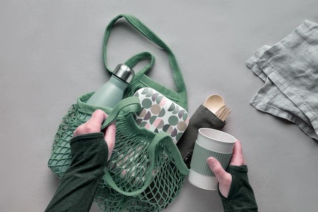 廃棄物ゼロのランチキット、コットンバッグにセットされた持ち帰り用のランチボックス、竹製のカトラリーのオーガナイザー、竹製のランチボックス、再利用可能なカップ。持続可能なライフスタイル、幾何学的なフラットレイアウト、ペーパークラフトのトップビュー。