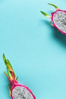 新鮮なオーガニックドラゴンフルーツ(ピタヤまたはピタハヤ)は、青いミントの壁を半分に切りました。コピースペースを持つ創造的なフラットなレイアウト。鮮やかな大胆なピンクとグリーンの色のトレンディなエキゾチックなフルーツ。