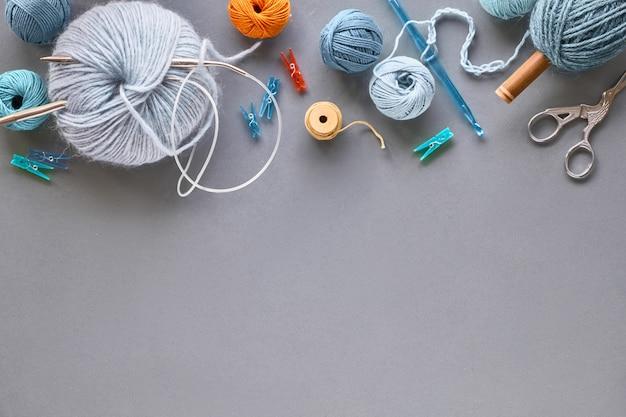 コピースペース付きの灰色の紙にパステルカラーの創造的な編み物趣味の壁
