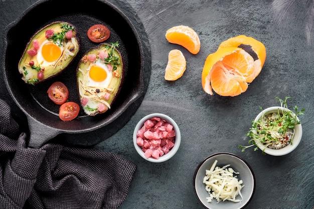 Кето диетическое блюдо: авокадо лодки с ветчиной кубиками, перепелиными яйцами, сыром, ингредиенты вокруг