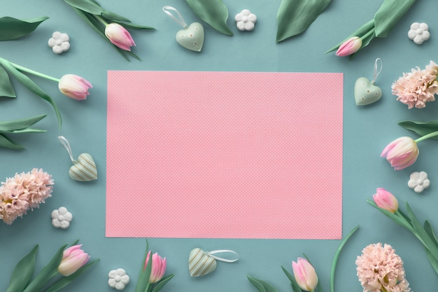 ピンクのチューリップ、ヒヤシンス、セラミック花、装飾的な心、テキスト領域と春の青い壁