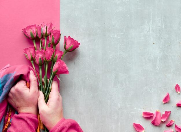 石の背景に斜めの幾何学的な紙。平干し、ピンクのバラと活気に満ちたトレンディなスカーフを持った女性の手が花びらを散らばっていました。トップビュー、バレンタイン、誕生日や母の日の挨拶。