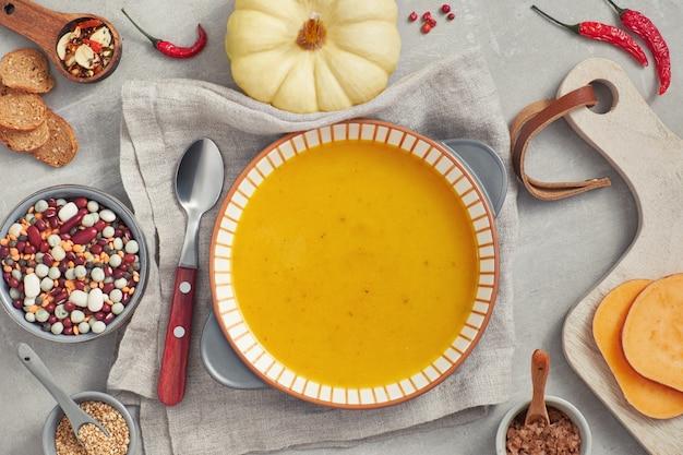 カボチャ、混合豆、セラミックボウルのサツマイモクリームスープ、食材とスパイスの上面図