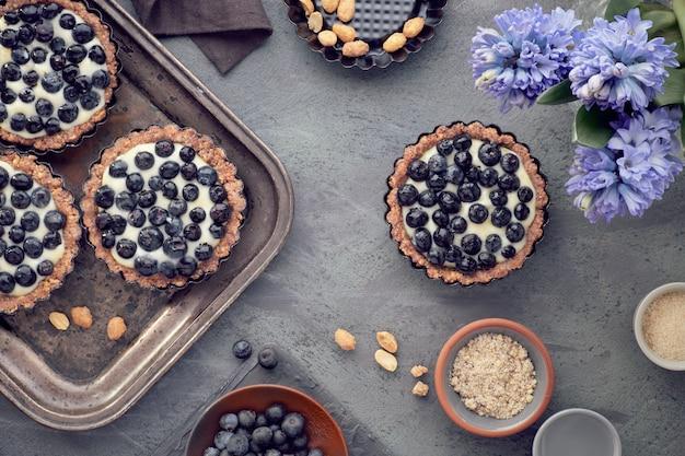 Вид сверху на цельнозерновые черничные пироги с ванильным кремом на темном