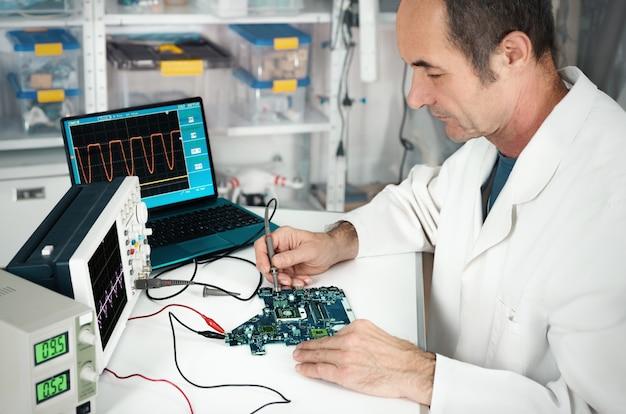 ハードウェア修理施設で上級技術者が働いている