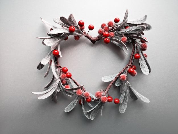 ハート型の装飾的なヤドリギのクリスマスリース、フラットは光のグラデーションの紙の壁に横たわっていた