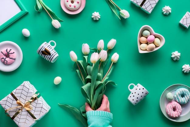 幾何学的な春のフラットは、緑のミントの背景に横たわっていた。イースター、母の日、春の誕生日または素朴なスタイルの記念日。手に白いチューリップ。イースターエッグ、コーヒーカップ、新鮮なチューリップ、ドーナツ