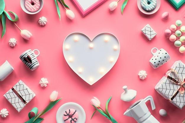 幾何学的な春のフラットは、ピンクの背景に白と緑に横たわっていた。イースター、母の日、春の誕生日または記念日。プラスチック熱ライトボード、イースターエッグ、コーヒーメーカー、カップ、チューリップ、ギフト。