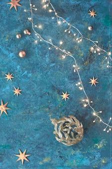 暗いグランジテクスチャボードにクリスマスや新年のフラットレイアウト背景。平面図、フラットはクリスマスライトガーランド、黄金のつまらないもの、小さな星のライトで横たわっていた。メリークリスマス、そして、あけましておめでとう!