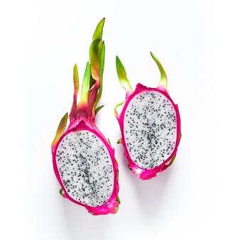 新鮮な有機ドラゴンフルーツ(ピタヤまたはピタハヤ)は、白い背景で隔離の半分にカット。鮮やかな大胆なピンクとグリーンの色でトレンディなエキゾチックなフルーツと創造的なフラットなレイアウト。