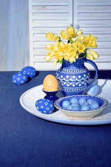 古典的な青と黄色の色のイースター装飾。水玉と黄色のフリージアの花、伝統的なセラミック花瓶、水差し、青いリネンのテーブルクロスのプレートとオレンジの卵。インテリアスプリングデザイン。