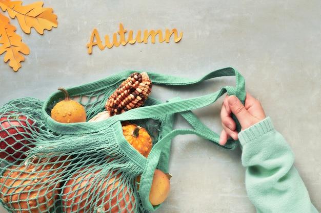 秋のフラットは、オレンジ色のカボチャとターコイズブルーのストリングバッグで横たわっていた、トップは灰色の石の上で争う