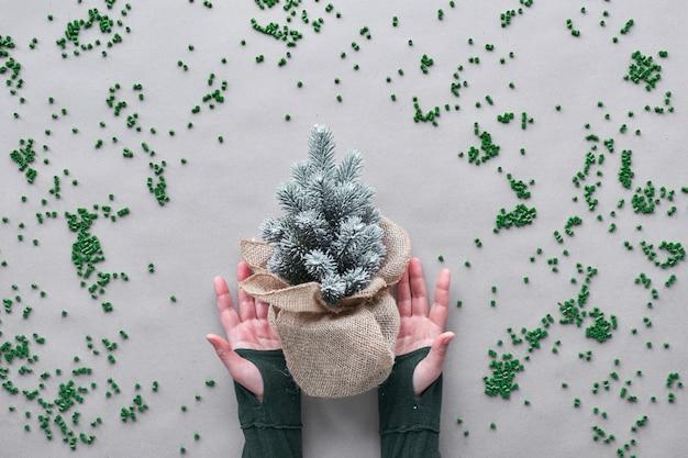 偽のプラスチック製のクリスマスツリーをできるだけ長く使用してください。代替グリーンエコフレンドリーなクリスマスコンセプト。手は黄麻布に包まれたプラスチックの木をクラフト紙に散らばったプラスチックで示しています。