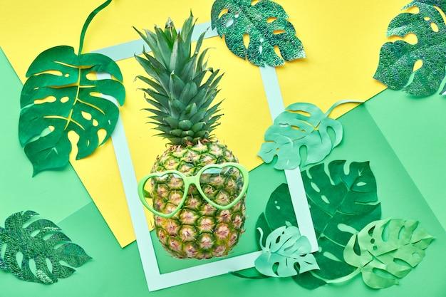 Смешной ананас в солнцезащитных очках, рамке и бумаге экзотических листьев в нео-мятной, зеленой и желтой
