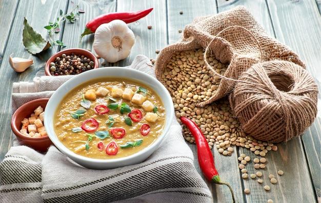 素朴な木製のテーブルに唐辛子、ニンニク、タイムのスパイシーなレンズ豆のスープ