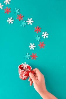 赤と白の季節の装飾が施されたカップを持っている女性の手。パステルブルーの紙の壁にフラット横たわっていた、トップビュー。