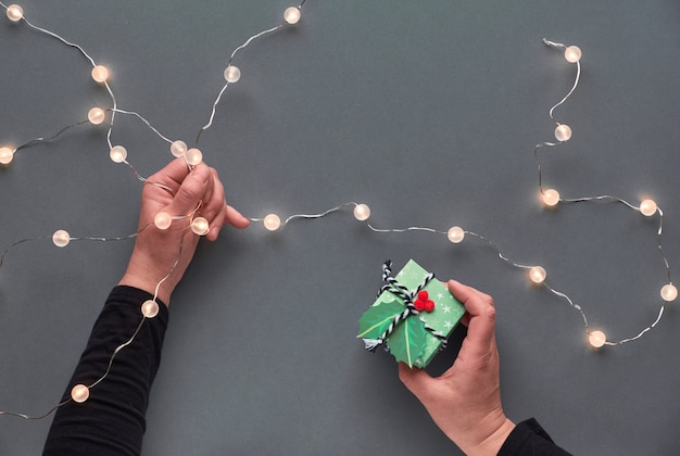 冬の休日のお祭りの構成。セラミックのモミの木の装飾を持っている手。正月やクリスマスフラットが横たわっていた。ヒイラギの手の中の光の花輪とギフトボックス。灰色の紙の壁にクリスマスのトップビュー。