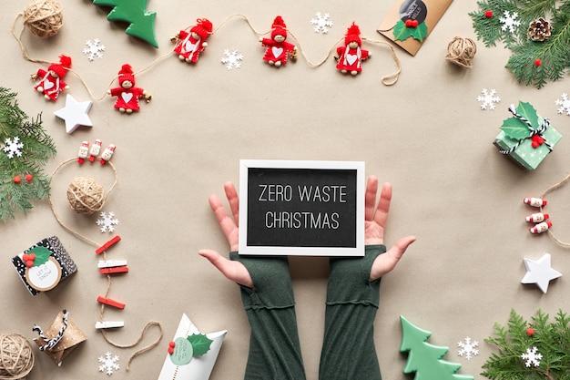 廃棄物ゼロの廃棄物、繊維人形のガーランドが付いたクラフト紙の壁のトップビュー、ラップされた贈り物、カラーペーパーに「ゼロ廃棄物クリスマス」というテキストが記載されたブラックボード。環境に優しいクリスマスの装飾。