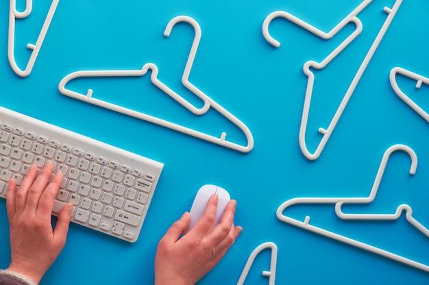 白いプラスチック製のハンガー、キーボードとコンピューターのマウスの手。創造的な平面図はパステルミントブルーの壁、創造的なミニマリズムの上に横たわっていた。トップビュー、販売、オンラインショッピングのコンセプト。